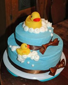 A Blue Cake with some cute brown bows in this rubber ducky themed cake.