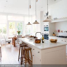 Der lichtdurchflutete Raum wirkt dank der weißen Einbauküche und den Holzelementen noch sommerlicher und natürlicher. Die Barhocker aus Naturholz sind ein Design-Statement …