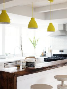 Stunning contemporary kitchen with adjustable wooden barstools lining a white kitchen island finished with a raw edge wooden waterfall counter illuminated by three yellow enamel pendant lights.