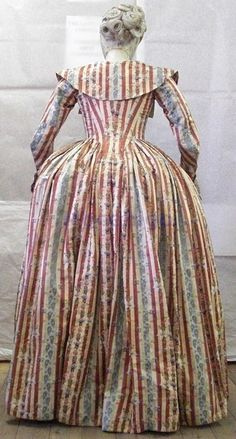 Back view of Redingote and matching petticoat dated 1779 - 1799. Pekin fabric and decorated with vertical grooves in cream and red with sprigs of roses. Lined in linen. The bodice has slats. Venice Costume, Museo Mocenigo       Museum number: Cl. XXIV no. 0,221