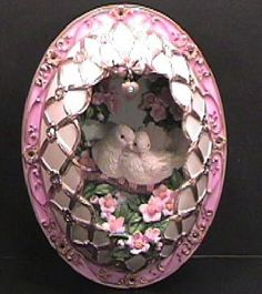 The Courtship: A 3-dimensional egg shape self hanging plate in the Carl Faberge Egg style. Richly gilded & finely detailed half shell contains the royal white swans. The outer shell is encrusted with pink Austrian crystals, gilded trellis & pink water lilies / glassmenagerie.co...