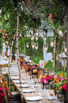 Simple hanging lanterns over table laid with tropical flowers for wedding party of 50 people.