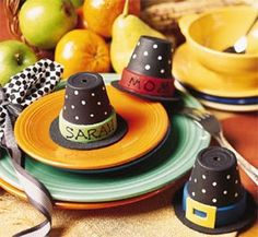 Miniature clay pots are painted black and the rims are painted various colors to resemble hat bands. A black fine point marker was used to write the names of your guests. The add the white polkadots simply use a white paint pen with an ultra fine point. Just dab the white paint on the black and allow to dry for 2-3 hours.
