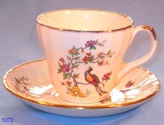 Aynsley Vintage Cherry Blossom Cup and Saucer Large Size Vintage Tea Cup and Saucer made by H. Aynsley & Co., Longton, Staffordshire Potteries, 1946-54. Fluted body decorated with exotic birds and boughs of blossom, finished with a gold trim. Good vintage condition. Cup height 7 cm; diameter 8.5 cm. Saucer diameter 14 cm