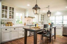 Episode 13 - The Worm House - Magnolia Market  White kitchen, detailed backsplash behind stove, wood accent on vent hood