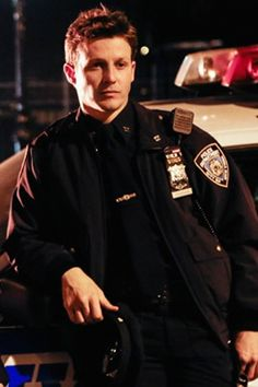 Will Estes in uniform leaning on a police car. What more could a girl want?