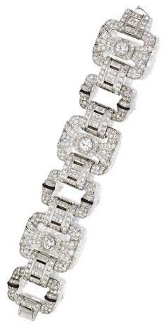 Platinum, diamond and black enamel bracelet, Circa 1930.  The three larger old European-cut diamonds weighing approximately 3.55 carats, smaller old European-cut and single-cut diamonds weighing a total of approximately 14.40 carats, square-cut diamonds weighing approximately 3.60 carats.