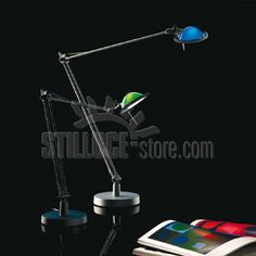 Luceplan Berenice D12 EL pi. lampada da tavolo coordinata con i modelli da parete e terra. Parti metalliche in pressofusione di alluminio nel colore alluminio o nero. Riflettore parabolico in vetro pressato nei colori verde, blu, bianco e rosso, oppure in metallo nei colori alluminio e nero.
