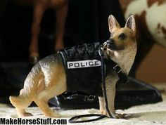 Admiral, the Schleich German Shepherd dog, has a new black bulletproof vest with a ring to attach a leash. The leash can tuck under the lacing on his back to keep it out of the way. The vest buckles under his stomach and on his shoulders. By MakeHorseStuff.com