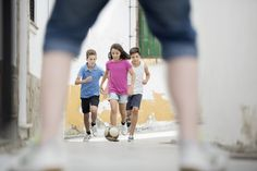 Children playing with soccer ball in alley by Caia Images - Photo 130418629 - 500px