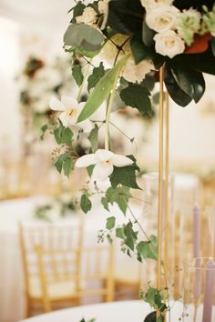 detail of tall wedding reception arrangement highlights white roses, magnolia, white tulips and vines cascading down the gold pedestal.