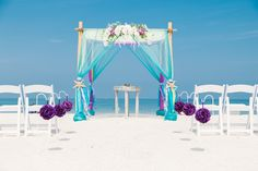Colorful turquoise and purple beach wedding arbor.
