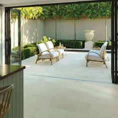 pale stone paving in kitchen through to patio/terrace courtyard garden with bi-fold doors pleached trees and central urn mounted onto plinth Stonemarket Isis Delta Sand Outdoor Rooms, Outdoor Living, Outdoor Furniture Sets, Indoor Outdoor, Outdoor Decor, Outdoor Ideas, Outdoor Seating, Outdoor Life, Paving Design