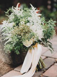 For a simple and rustic wedding bouquet, fill it with Queen Anne's lace, privet berries and an abundance of greenery.