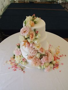 cream, peach and pink garden roses on a cake.