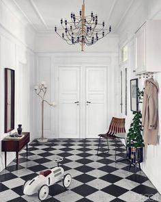 A STOCKHOLM ENTRY  Stylist Joanna Lavén and David Wahlgren installed checkered marble flooring in the entry of their Stockholm apartment. The chandelier is a 1958 Gino Sarfatti design from Flos, the sideboard is by Arne Vodder, and the floor lamp is Italian; the chair is from Scandia Chair, and the plant stand is by Fornasetti.