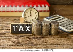 coins stack with time and wording tax on wooden tag,concept for tax of time or business. Pay Taxes, Wooden Tags, Photo Editing, Coins, Royalty Free Stock Photos, Place Card Holders, Concept, Business, Marketing