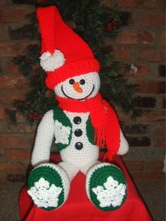 "We all knew that he would come back again!!! Even though the days are sweltering now, we will see snow again. This precious snowman is made out of worsted weight yarn and can be made in the Christmas colors as shown or in blue shades so he can keep you company through the whole winter season. He's approximately 19"" tall with his hat folded down. He has ""charcoal"" buttons on his chest and a scarf wrapped around his neck."