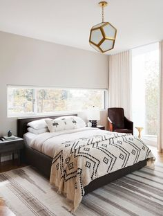 Neutral bedroom with octagonal lantern fixture and stripe rug.