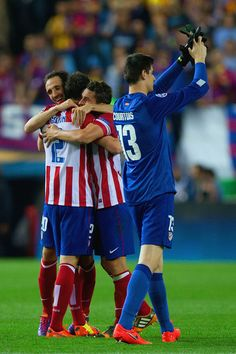 Diego Godin, Juanfran and Koke of Club Atletico de Madrid hug as Thibaut Courtois of Club Atletico de Madrid applauds the fans during the UEFA Champions League Quarter Final second leg match between Club Atletico de Madrid and FC Barcelona at Vicente Calderon Stadium on April 9, 2014 in Madrid, Spain.