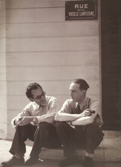 """Man Ray and Marcel Duchamp sitting beneath a Parisian street sign, """"Rue de la Vieille Lanterne"""", on a stage set in Hollywood. L.A., California, 1949"""