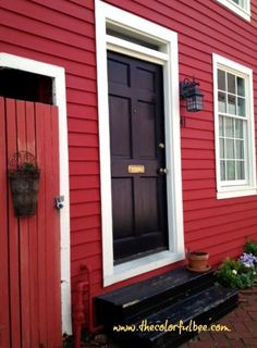 Red house with white trim and a black door.
