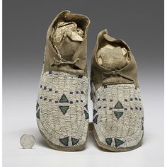 Cheyenne Beaded Hide Moccasins sinew-sewn and beaded using colors of white, dark blue, and pea green; angled cuffs, length 9.25 in. late 19th century Price Realized Including Buyer's Premium $540 08/11/2016