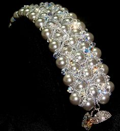 """This gorgeous South Sea Shell Pearl bracelet is bead-woven in classic platinum using 8mm pearls, 4mm Swarovski crystal AB bicones, Miyuki seed beads, secured with a silver-plated, rhinestone-encrusted super-strong magnetic clasp. The bracelet measures 7.5"""" from clasp to clasp and is 1.25"""" wide. """"Celastrina"""" is an elegant, formal design suited for weddings or any formal engagments."""