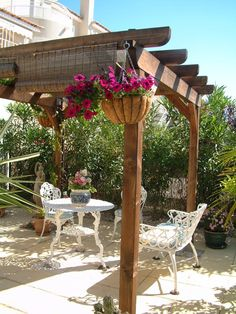 Pergola over patio with white wrought iron patio furniture. <3 the bamboo shades...