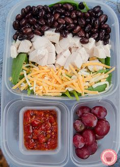 Spinach salad with chicken, black beans and shredded cheese, grapes and crushed red peppers.