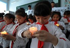 Pupils holding candles mourn during a silent tribute in Harbin, capital of northeast China's Heilongjiang Province