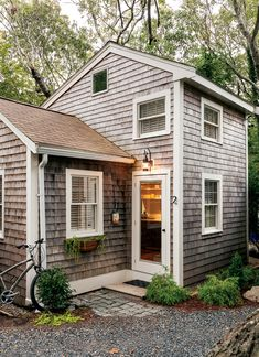 Cape Cod Bungalow--a 350-square-foot vacation cottage in a wooded setting overlooking Provincetown wetlands.Such efficient use of a small space while retaining a sense of openness and grace. I love the juxtaposition of the traditional exterior contrasted with a sleek mid-century modern interior. The grey and white interior paint scheme echoes the clapboard and is a fresh, neutral background for all accent colors.