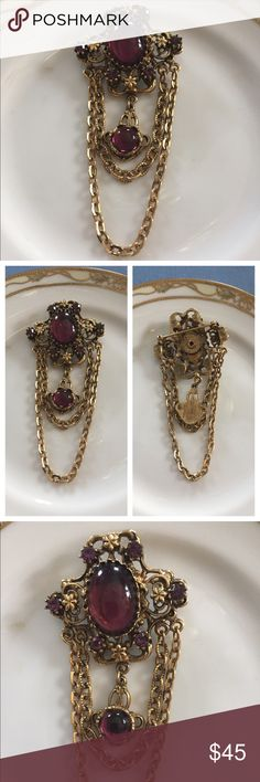 """Vintage Amethyst Chatelaine Brooch Pin This is such a beautiful and quality-made ornate filigree Maltese cross-shaped gold-tone chatelaine brooch. This vintage 80's pin features an oval faux amethyst cabochon with an attached dangling round faux amethyst cabochon, two draping chains, and the ends of the cross section are dotted with faux amethyst crystals. Back has a c-clasp. Unmarked. Measures a total of 2-1/2"""" l x 1-1/2"""" w. In excellent preowned condition. Vintage Jewelry Brooches"""