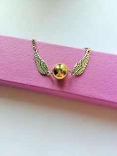 Handmade Harry Potter Golden Snitch Bracelet! It comes all packaged up in a lovely lilac HollieCraft bracelet Gift Box.  It almost 10 long including the 2 extender. This would make an amazing magical gift for the Harry Potter fan in your life. Makes a Fantastic Gift!    Please note that these are not Sterling Silver. They are just silver plated. Avoid direct contact with Perfume and water.  **Disclaimer all my items are handmade and created & inspired by TV / Book & Film I do NOT in any way…