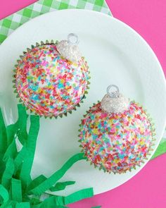 Learn how to make these epic Christmas ornament cupcakes with our full blog tutorial. Use any sprinkles of any color to make a perfect Christmas kids activity. These are the perfect addition to your Christmas party this year! #christmascupcakes #ornamentcupcakes #christmasornaments #sugarcrystals #diyornamentcupcakes