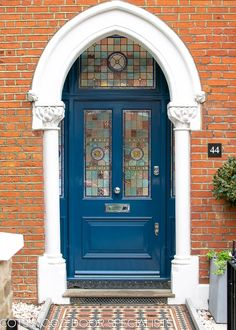 Victorian front entrance door with stained glass set into a classic Victorian Gothic arch. Door and door frame painted gloss blue