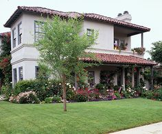 The generous foundation plantings of this Mediterranean-style home tie the house to the surrounding lawn and landscape. The homeowner chose plantings at all levels to embellish the two-story lines of the house as well as the front porch and two balconies.