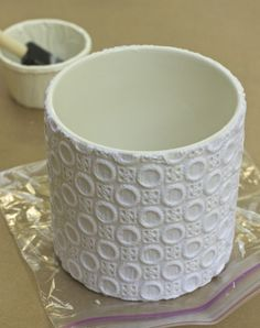 Mod Podge lace onto container. Wrap lace or knitted goods -- for texture -- onto container. Cover with a thin layer of plaster.