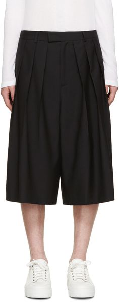 Pleated wide-leg wool shorts in black. Seam pockets at sides. Zip-fly. Tonal stitching.