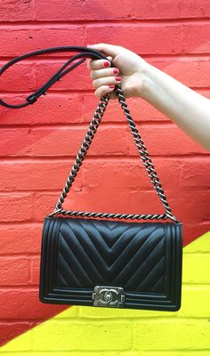 Chanel boy bag!!! black chevron against a painted wall, rainbow graffiti wall east london shoreditch, hands in frame