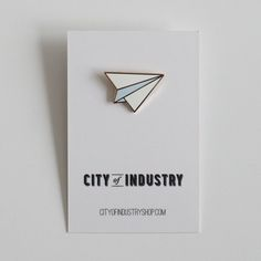 Maybe you used to disrupt class by passing notes, or maybe you're still day-dreaming of far-off places. Or maybe you just like folding paper. Either way, we think this paper airplane will look great on you.Cloisonne pin with gold-plating, approximately 1 inch by .75 inch in size.