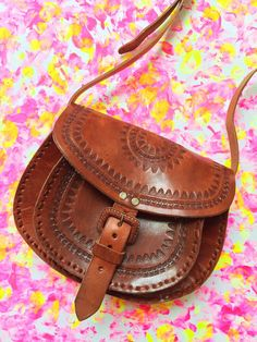 This stunning cross-body handbag was hand-made in Chiapas, Mexico, features a front pocket and beautiful hand tool work. Height: 17 cm x Length: 22 cm - All Prices are in CAD Dollars - Boho Crossbody Bag, Cross Body Handbags, Beautiful Hands, Handmade Gifts, Handmade Products, Saddle Bags, Purses, Unique Jewelry, Summer 2016