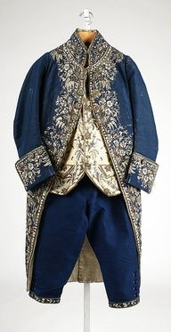 This 18th century men's suit is fashioned from navy blue and ivory silk and decorated with elaborate embroidery and goldwork, as was popular for the duration of the period. Note the high, military inspired collar and fold-over cuffs.