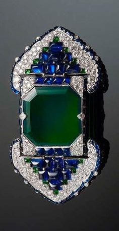 Belt Brooch by Cartier, circa 1920-30. Platinum, set with emeralds, sapphires and diamonds
