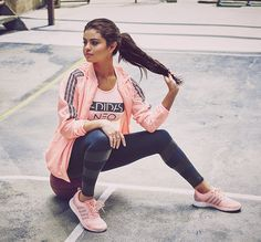 Selena Gomez sits on a basketball in Adidas Neo Fall 2015 campaign in a pink jacket, pink shoes and leggings. She also stars in the campaign video.