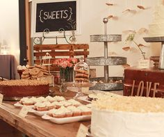 A small glass bell jar and tin three-tiered dessert stand compliment the wood elements of this wedding dessert table.