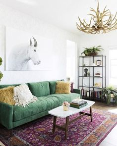 Green couch with purple and red rug surrounded by white walls and antler chandelier