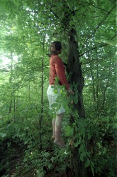 """Darko Bandio - July 1995.Tuzla.  """"I was approached by a group of three or four young girls that told me about a woman who hung herself on the tree nearby.They took me to some woods where I saw the surreal scene: a woman wearing a red cardigan looking more like levitating than hanging, several meters above the ground, surrounded by green leaves.    Read more: http://lightbox.time.com/2012/04/05/bosnia/#ixzz1rKMqXzid"""""""