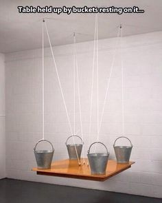 """""""Pretty sure this breaks physics, but that is awesome."""" ..The four buckets merely equalize the weight of the table, still awesome though :P"""