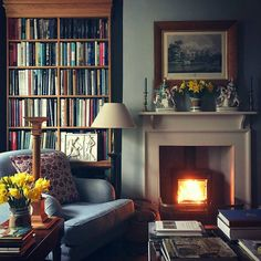 Love the wood stove inside of the fireplace. Colors and fabrics are great, too.
